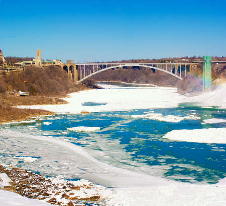Rainbow Bridge at Niagara Falls in the winter with ice and snow on the river