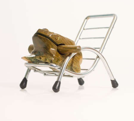Carved frog sitting in a silver beach chair photo