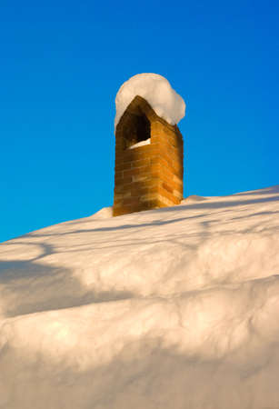 Chimney that is covered in snow photo