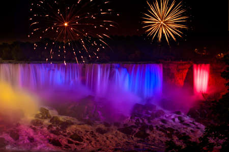 Rainbow colored Niagara Falls with fireworks display