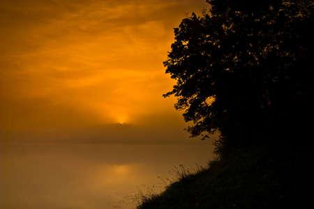 Hazy smoggy morning sunrise shining through photo