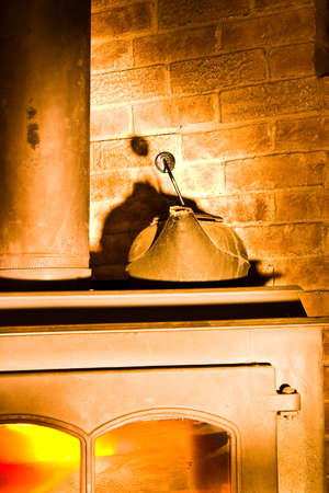 Water Kettle on a warm fireplace in a corner Stock Photo - 3841193