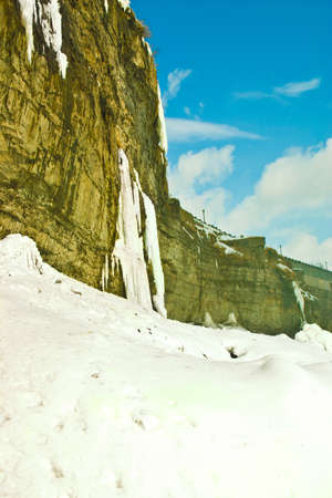 The side of a mountain cliff covered in snow