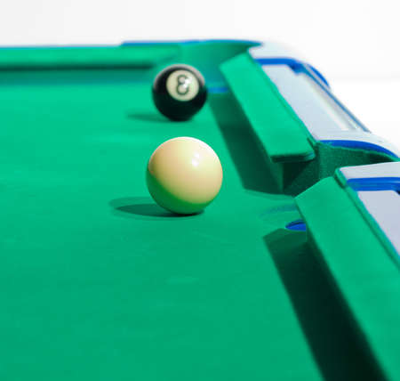 Game of pool being played on felt table