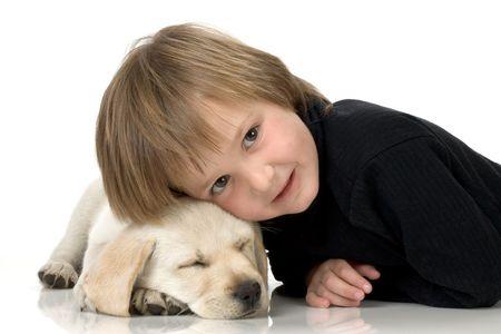 Child lying with head on sleeping Labrador retriever puppy Reklamní fotografie