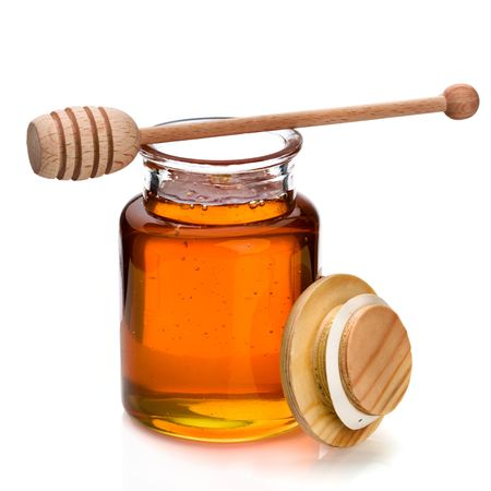 Honey in a glass jar with wooden dripper on top