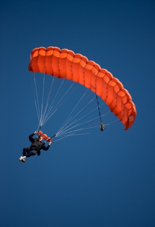 Parachuter descending with a red parachute against blue sky Stok Fotoğraf