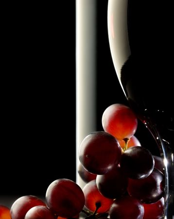 Close-up of red grapes with glass and bottle in background Reklamní fotografie