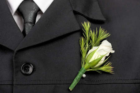 White rose pinned on jacket of groom on wedding day photo