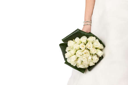 Wedding bouquet of white roses and green leaves in brides hands