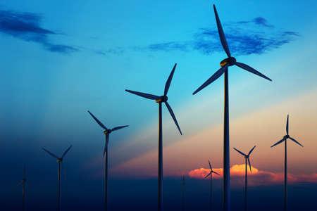 eficiencia energetica: Granja de turbinas de viento con rayos de luz al atardecer  Foto de archivo