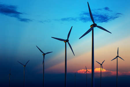 Wind turbine boerderij met stralen van het licht bij zons ondergang  Stockfoto
