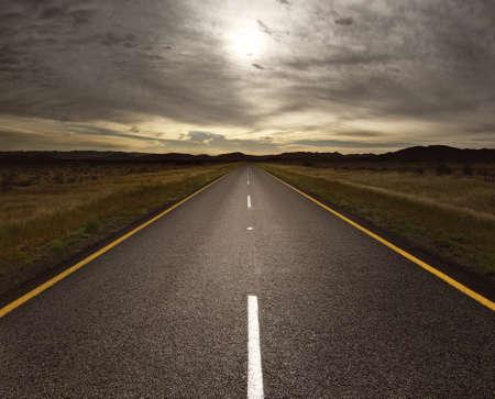 Rechte teer weg die leidt naar het licht (getinte afbeelding)