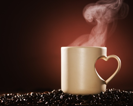 Mug of hot coffee on coffee beans with rising steam Stock Photo - 9527689