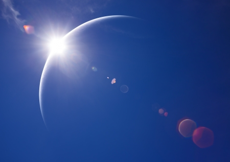 Partial Solar Eclipse with blue sky and lens flare photo