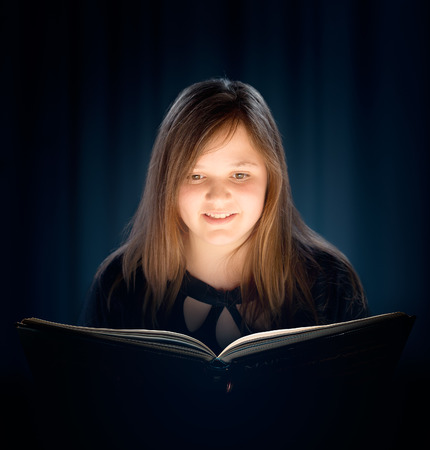 Young girl with long hair reading a book with glowing light