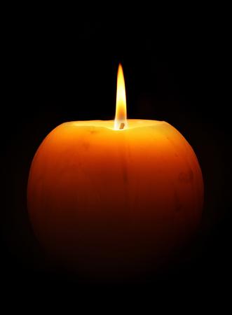 Burning round big orange candle