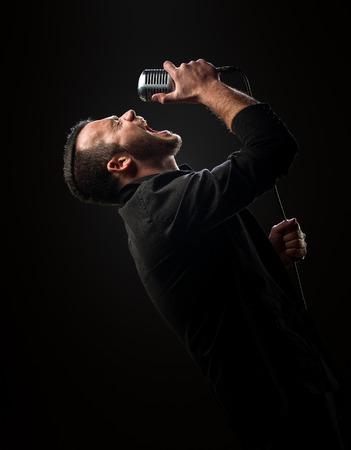 Chanteur jouant avec microphone sur un fond sombre Banque d'images - 43182675