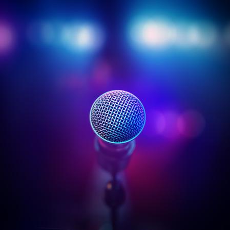 Muzikale microfoon close-up van achter geconfronteerd onscherp stadiumlichten Stockfoto