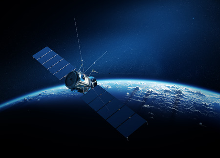 Communications satellite orbiting Earth with sunrise in space