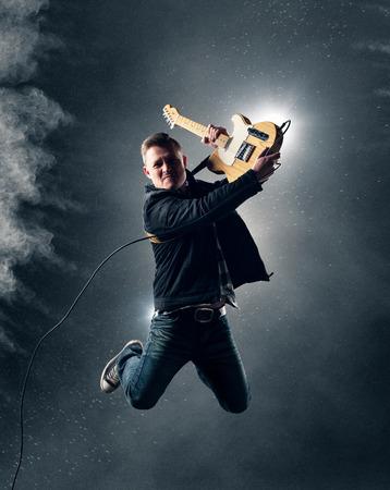ロックン ロールのギタリストが煙とバック グラウンドでパウダーでエレク トリック ギターとジャンプ