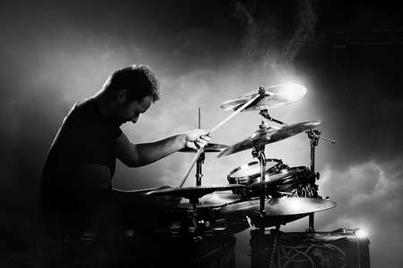 Drummer playing the drums with smoke and powder in the background