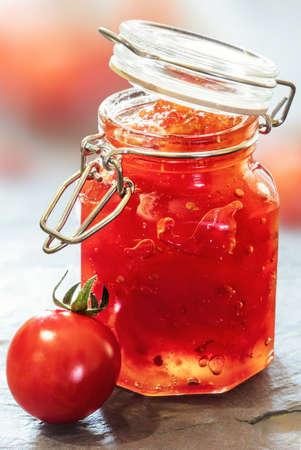 슬레이트 테이블 위에 유리 항아리에 토마토 잼