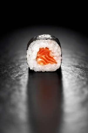 Maki sushi roll avec saumon et riz enveloppé dans nori sur un fond noir Banque d'images - 97151811