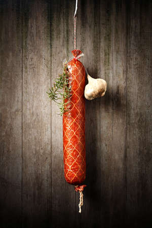 Salami Sausage hanged to dry with Garlic and Rosemary against an old rustic wooden wall