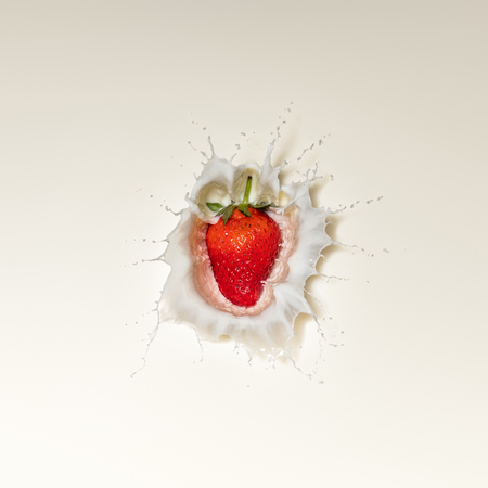 Fresh Red Strawberry fruit splash in white milk and viewed directly from above Reklamní fotografie