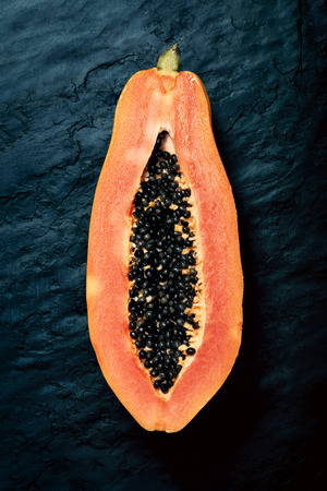 Papaya (Paw Paw) sliced in half and viewed from above on dark blue black slate rock 스톡 콘텐츠