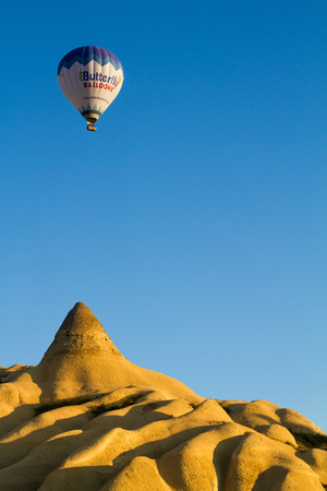 Hot air balloon flying in the morning sky over the rocky landscape of Cappadocia, Anatolia, Turkey.