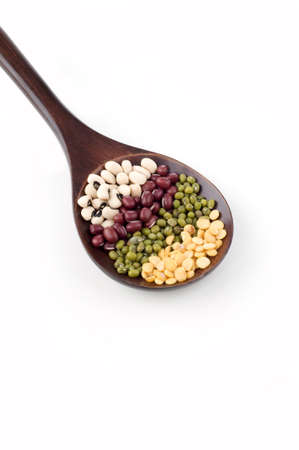 Dry legumes on brown spoon isolated white background photo