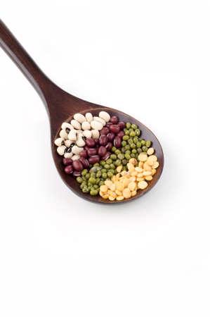 leguminosas: Legumbres secas en la cuchara de café aislado fondo blanco Foto de archivo