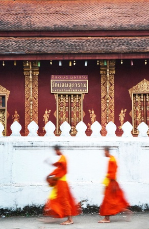 Dawn procession of monks receiving alms from townspeople in Luang Prabang. Laos