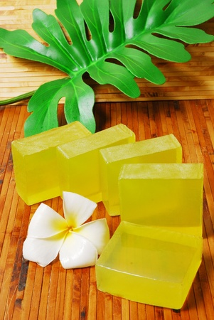 Handmade soap bars on Bamboo mat with Frangipani flowers and leaf.