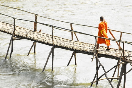 Monks crossing a wooden bridge in Luang Prabang, Laos  Editorial
