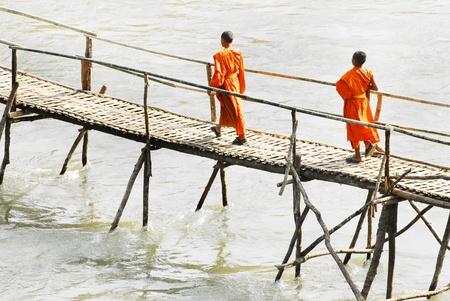 Monks crossing a wooden bridge in Luang Prabang, Laos