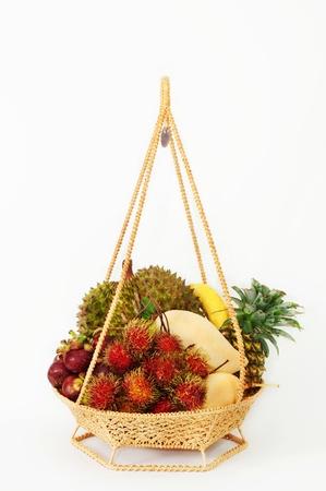 canasta de frutas: Frutas tropicales en la cesta de estilo tailand�s, aislado sobre fondo blanco Foto de archivo