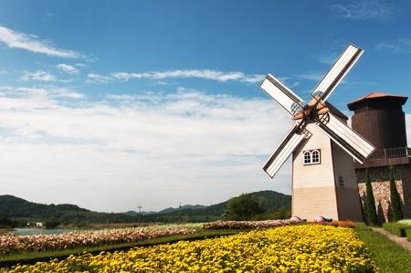 bluer: Wooden windmill on blue sky background