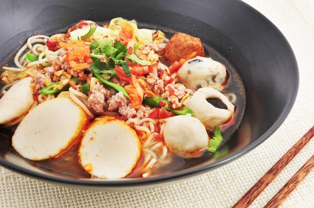 eating noodles: Hot and Spicy noodle soup with fish ball