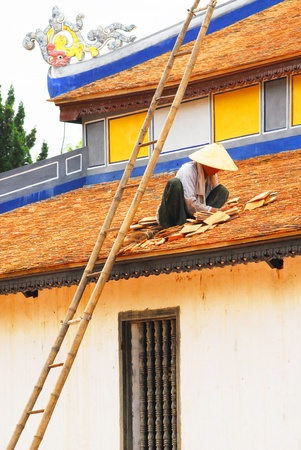 porter house: Vietnamese people are repairing the roof