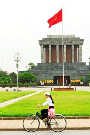 Vietnamese woman riding a bicycle and Ho Chi Min mausoleum in Hanoi  Vietnam