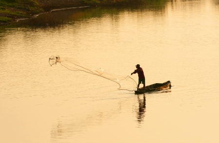 A man throw fishing net in evening, Thailand photo