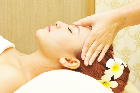 A young woman receiving a head massage in a spa  photo