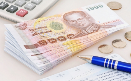 financial statement: Calculator and pen on thai banknotes