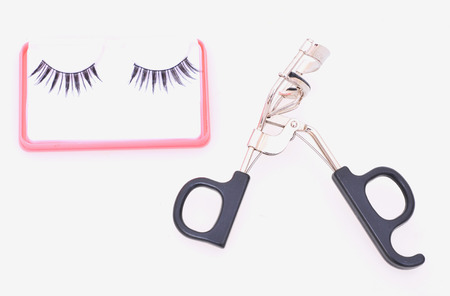 False eyelashes and eyelash curler  on a white background photo