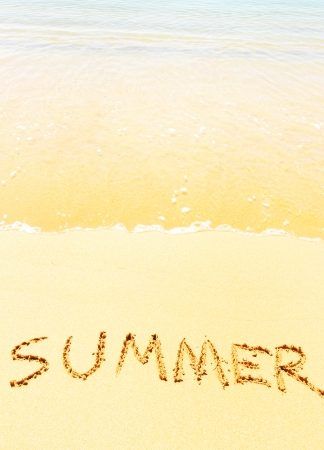 Summer - text written by hand in sand on a beach, with a soft wave  photo