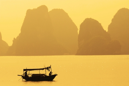 A boat sailing along the coast of Halong Bay, Vietnam photo