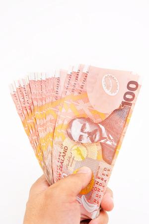 new economy: Hand holding new zealand doller on white background.